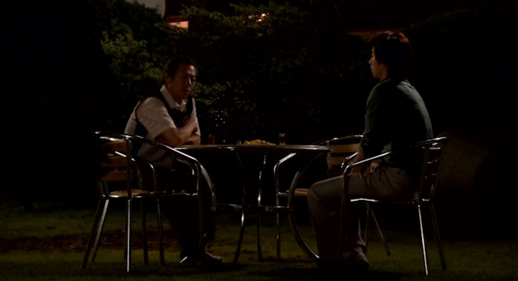 Han-gyul and his father sitting across the table from each other